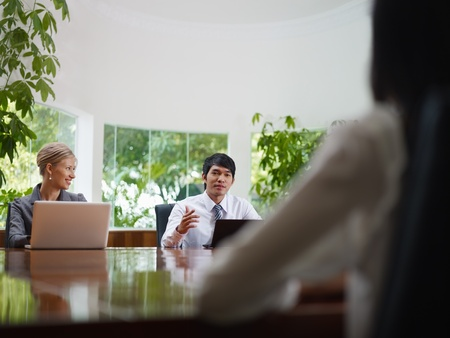 Young business people with laptop computers at meeting in conference room. Front view, copy space Stock Photo - 11918219