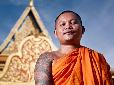monk: Mid adult Asian monk smiling at camera in buddhist monastery, Phnom Penh, Cambodia, Asia. Low angle Stock Photo