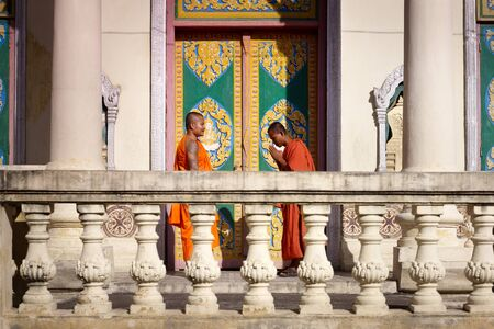 Two young buddhist monks meeting and saluting in a temple, Phnom, Penh, Cambodia, Asia. Side view photo