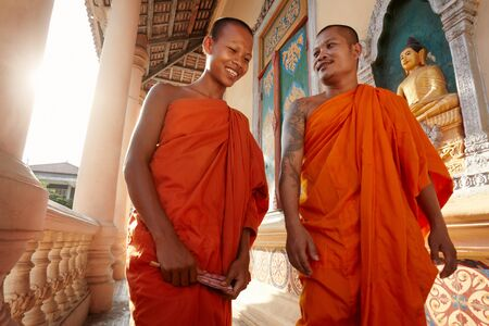 Two buddhist monks meeting and saluting in a temple, Phnom, Penh, Cambodia, Asia. Dolly shot photo