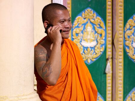 mid adult buddhist monk speaking with cell phone in monastery, Phnom Penh, Cambodia, Asia photo