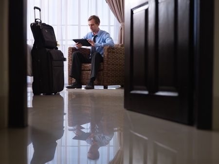 Mid adult caucasian manager typing on tablet pc in hotel room during business travel. Low angle view, full length photo