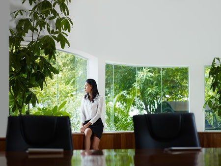 Beautiful Asian female manager looking out of the window in office. Front view, copy space photo