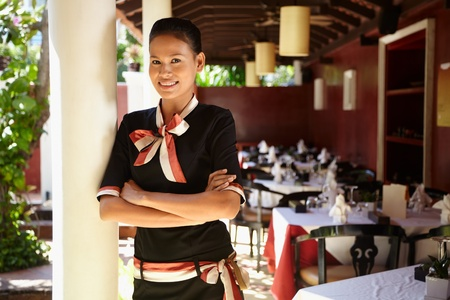 waist up: Portrait of attractive young asian woman working as waitress in exclusive restaurant. Waist up, front view Stock Photo