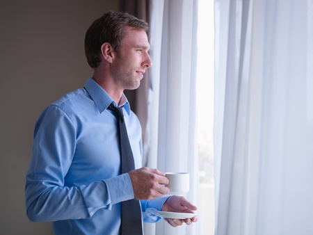 Mid adult business man relaxing and drinking a cup of tea, looking out of window. Side view, copy space photo