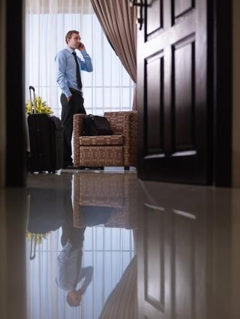 maletas de viaje: Cauc�sicos mediados de hombre de negocios de adultos hablando con tel�fono m�vil en la habitaci�n de hotel durante el viaje de negocios Foto de archivo