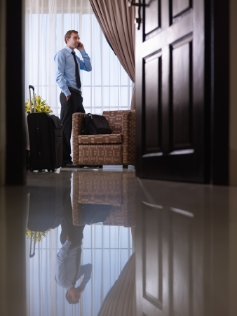 hotel room door: Caucasian mid adult businessman talking with mobile telephone in hotel room during business trip Stock Photo