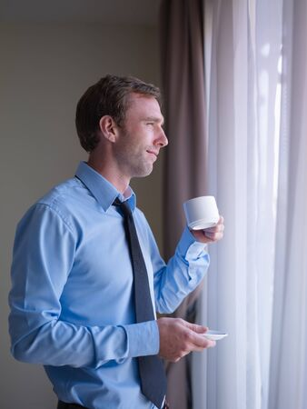 man looking out: Mid adult business man relaxing and drinking a cup of tea, looking out of window. Side view