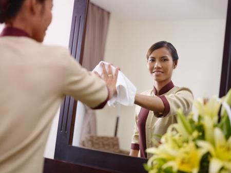 Retrato de ama de llaves de Asia feliz en el trabajo en la habitación de hotel de lujo y sonriendo a la cámara Foto de archivo