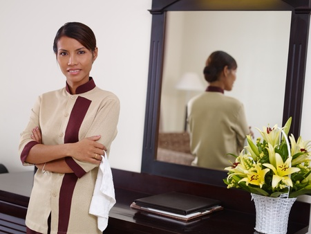criada: Retrato de ama de llaves de Asia feliz en el trabajo en la habitaci�n de hotel de lujo, y sonriendo a la c�mara