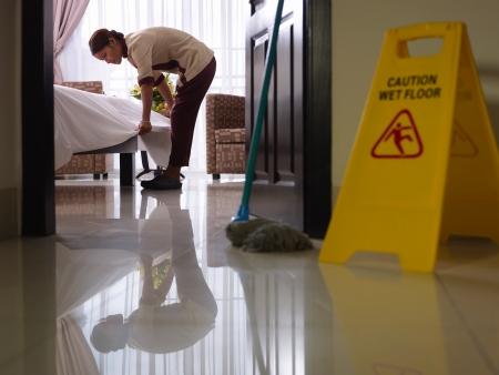 huis opruimen: Aziatische meid opruimen bed en het reinigen van luxe hotelkamer