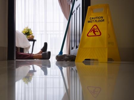 accidente trabajo: doncella tuvo accidente de trabajo durante la limpieza de piso en la habitación de hotel. Vista lateral, ángulo bajo