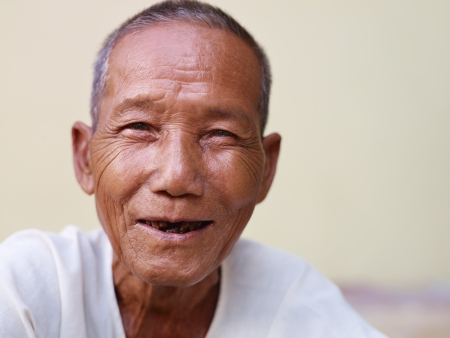 Portrait of happy senior asian man with dental problems laughing and looking at camera against yellow wall photo