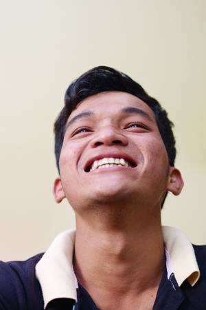 Portrait of happy young asian man smiling and looking up against yellow wall. Copy space photo