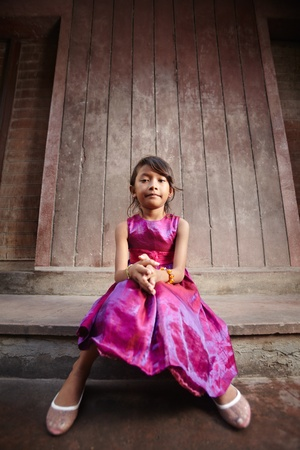 Portrait of cute Asian female child in pink dress looking at camera photo
