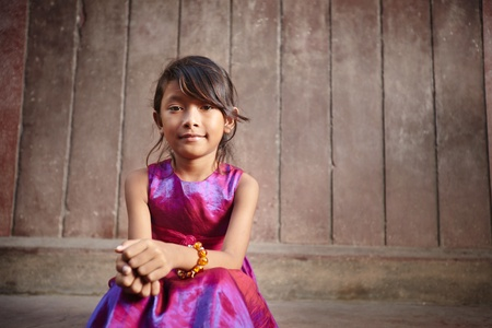 Portrait of cute Asian female child in pink dress looking at camera. Copy space photo