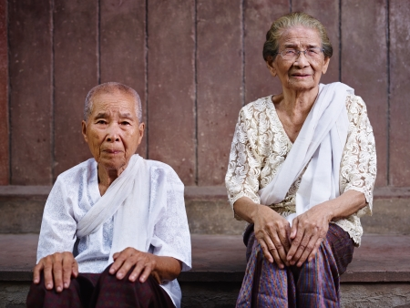 Portrait of two old asian women sitting against brown wall and looking at camera photo