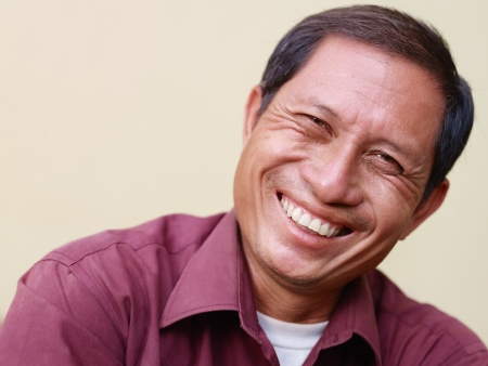 Portrait of happy mature Asian man smiling and looking at camera. Copy space photo