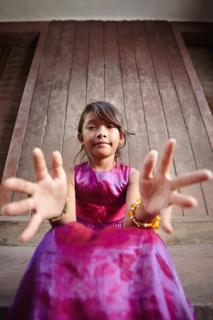 Portrait of cute Asian female child in pink dress pointing hands at camera photo