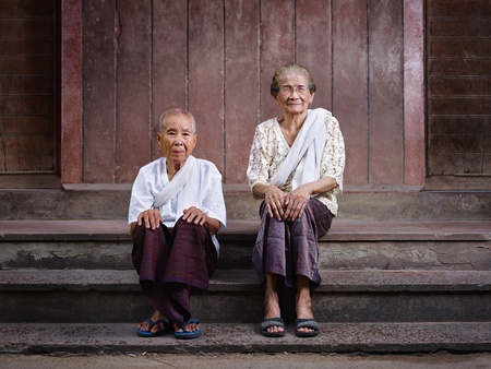 southeast asia: Portrait of two old asian women sitting on steps out of their house and looking at camera