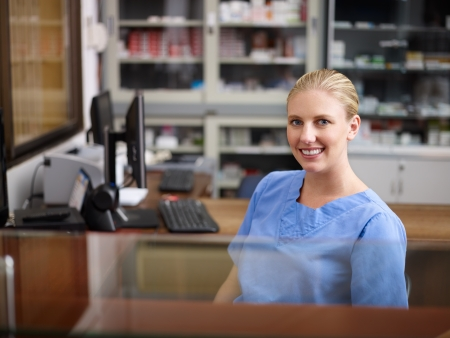 Young woman at work as receptionist and nurse in hospital, looking at camera