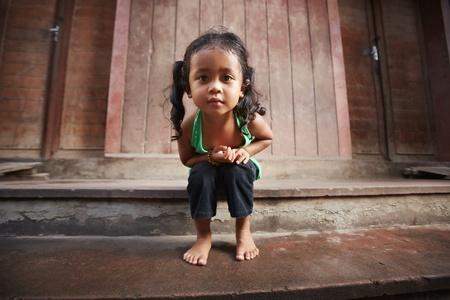 Retrato de niño lindo asiático femenino en camiseta verde que se sienta en la calle y mirando a la cámara
