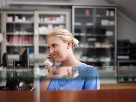 recepcionista: Joven mujer en el trabajo como recepcionista y la enfermera en el hospital y hablar por teléfono