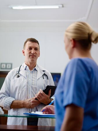 Doctor talking to young woman at work as nurse in medical clinic and taking medical file.  photo