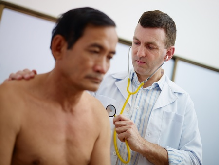 caucasian doctor working and visiting old asian male patient in hospital with stethoscope photo