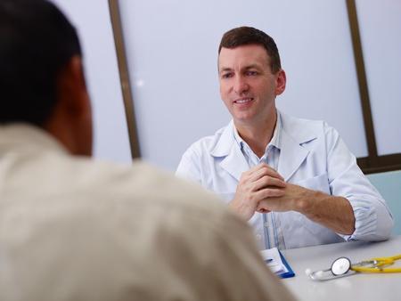 Doctor patient: Doctor amigable de trabajo y dar asistencia a los pacientes de sexo masculino en la oficina del hospital. Enfoque en el fondo Foto de archivo