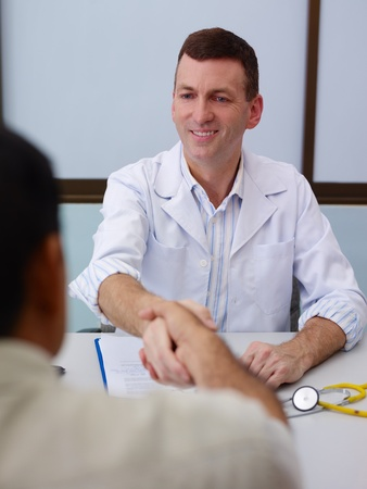 Friendly doctor working and handshaking old male patient in hospital office. Focus on background photo