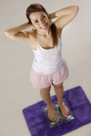 Mid adult happy caucasian woman on scales at home expressing satisfaction and joy for losing weight. High angle view Stock Photo - 12943209
