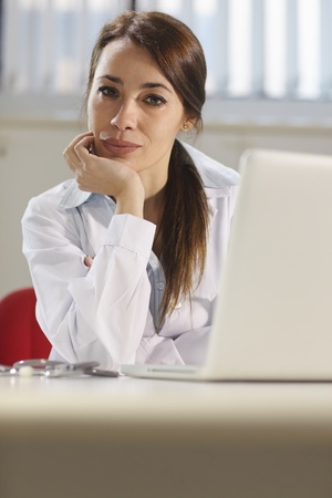 Portrait of mid adult attractive woman smiling at work as doctor with pc in hospital office. Copy space photo