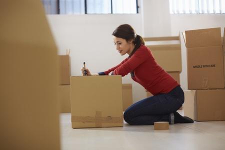medio volwassen gelukkige vrouw tijdens een beweging met dozen in nieuw vlak en doos Stockfoto