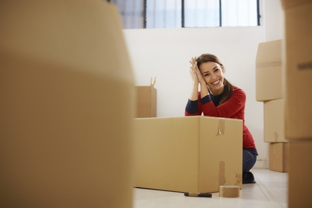Portrait of mid adult happy woman moving with boxes at new apartment and looking at camera. Copy space Stock Photo - 12943223