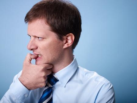 fingernail: stressed mid adult businessman biting fingernails against blue background. Copy space
