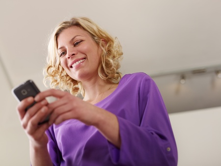 Young beautiful caucasian blonde woman typing e-mail message on smartphone and laughing  Low angle view, copy space photo