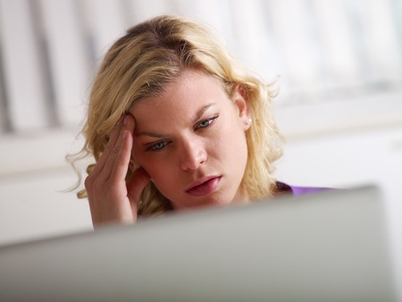 Young beautiful caucasian blonde businesswoman working with laptop computer and having headache for stress photo