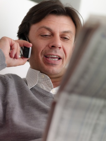 listings: Portrait of happy caucasian middle aged man sitting on sofa at home, reading stock exchange listings on newspaper and talking on cordless with trader