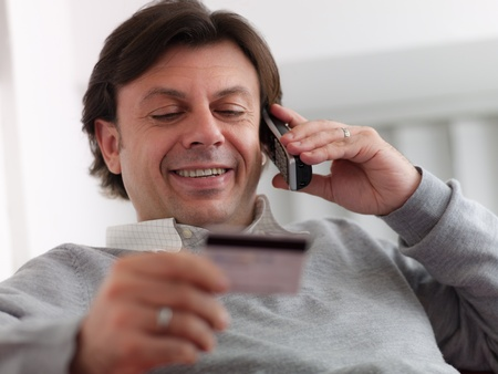 SATISFIED: Portrait of happy caucasian middle aged man sitting on sofa, talking on cordless and buying with credit card