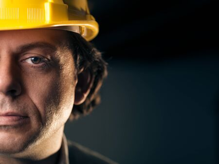 Portrait of serious middle aged man working as construction worker with hardhat. Copy space Stock Photo