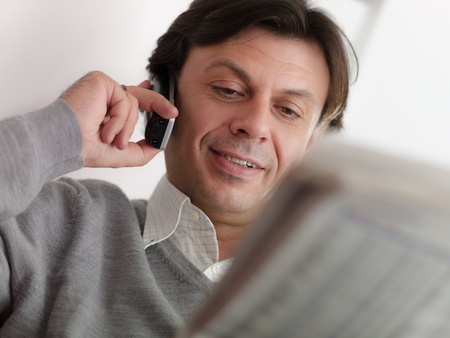 financial newspaper: Portrait of happy caucasian middle aged man sitting on sofa at home, reading stock exchange listing on newspaper and talking on cordless with trader