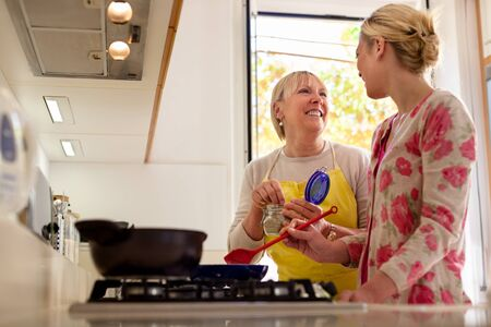Happy mother and daughter having fun while preparing food and cooking together in kitchen at home photo
