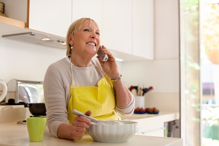 Happy senior woman at home, cooking in kitchen and talking on the phone photo