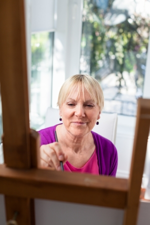 Happy retired woman painting on canvas for fun at home photo