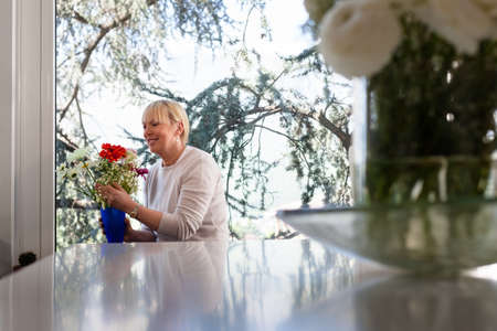 Senior caucasian woman with bunch of flowers in living room at home Stock Photo - 13408889