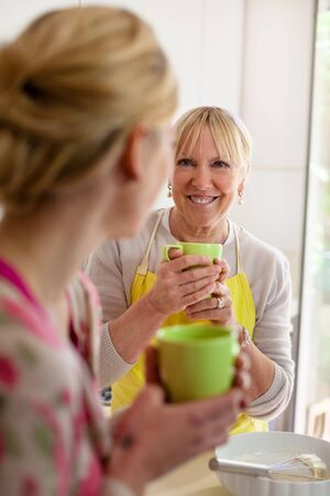 Happy women in home kitchen: mom and daughter talking and drinking a cup of tea photo
