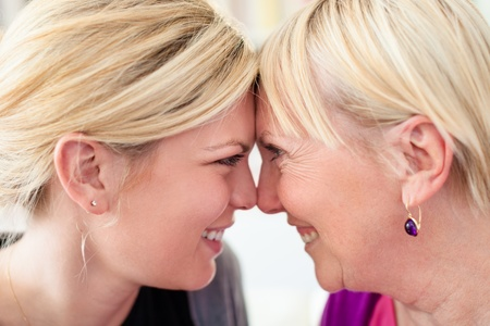 Women portrait with happy mom and daughter smiling, face to face, showing love and affection. Close up photo