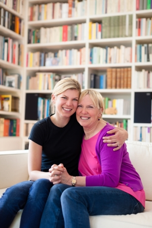 Women portrait with happy mom and daughter smiling and hugging at home, showing love and affection photo