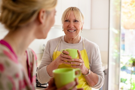people drinking coffee: Happy women in home kitchen: mom and daughter talking and drinking a cup of tea